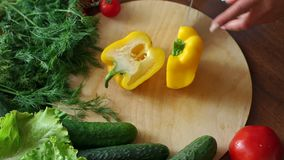 Close-up of a woman cuts in half fresh yellow bell peppers on a cutting Board. Close-up of a woman chef cuts in half fresh yellow bell peppers on a wooden stock footage