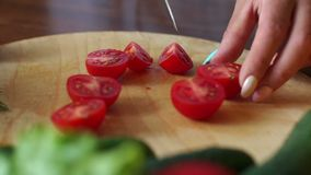 Close-up of a woman chef cuts a ripe tomato on a wooden chopping board. Slow motion stock video
