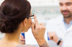 Close up of woman choosing glasses at optics store Royalty Free Stock Image