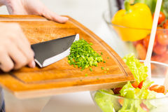 Close up of woman with chopped onion cooking salad Royalty Free Stock Images