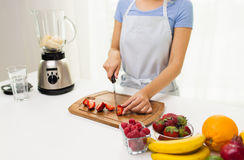 Close up of woman chopping strawberry at home Stock Photography