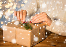 Close up of woman with christmas gift or parcel. Christmas, holidays, presents, new year and people concept - close up of woman decorating gift box or parcel Stock Photography