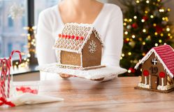 Close up of woman with christmas gingerbread house. Holidays, pastry and bakery concept - close up of woman holding and showing gingerbread house at home over royalty free stock photography
