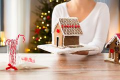 Close up of woman with christmas gingerbread house. Holidays, pastry and bakery concept - close up of woman holding and showing gingerbread house at home over stock images