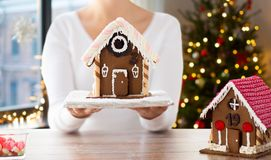 Close up of woman with christmas gingerbread house. Holidays, pastry and bakery concept - close up of woman holding and showing gingerbread house at home over royalty free stock images