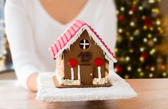 Close up of woman with christmas gingerbread house. Holidays, pastry and bakery concept - close up of woman holding and showing gingerbread house at home over stock photography