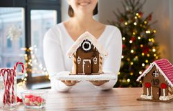 Close up of woman with christmas gingerbread house. Holidays, pastry and bakery concept - close up of woman holding and showing gingerbread house at home over stock image