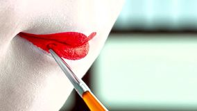 Close up of a woman with classic japanese make up on her lips. Geisha with red lips. Makeup concept stock images