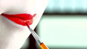 Close up of a woman with classic japanese make up on her lips. Geisha with red lips stock image