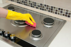 Close up of woman cleaning cooker at home kitchen royalty free stock image