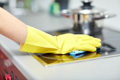 Close up of woman cleaning cooker at home kitchen. People, housework and housekeeping concept - close up of woman hand in protective glove with rag cleaning Stock Photo
