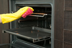 Close up of woman cleaning oven at home kitchen Royalty Free Stock Photo