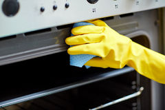 Close up of woman cleaning oven at home kitchen Stock Photography