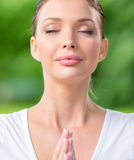Close up of woman with closed eyes prayer gesturing. Concept of healthy lifestyle and Buddhism Stock Image