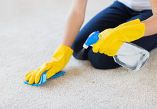 Close up of woman with cloth cleaning carpet Royalty Free Stock Image