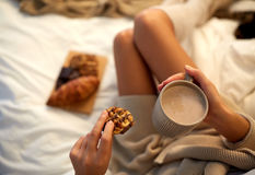 Close up of woman with cocoa cup and cookie in bed Royalty Free Stock Image
