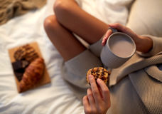 Close up of woman with cocoa cup and cookie in bed Stock Images