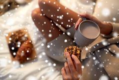Close up of woman with cocoa cup and cookie in bed Royalty Free Stock Photos