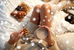 Close up of woman with cocoa cup and cookie in bed Royalty Free Stock Images