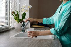 Close-up of a woman collects water in a plastic glass from the tap in the kitchen sink in front of the window.  royalty free stock images