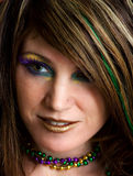Close-Up Of Woman With Colorful Makeup. A close-up portrait of a beautiful woman wearing bright, colorful makeup and matching beaded necklaces Stock Images