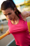 Close up of woman concentrating while doing tricep dips. Stock Photo