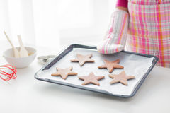 Close up of woman with cookies on oven tray Stock Photos