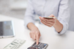 Close up of woman counting money with calculator Stock Photography
