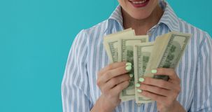 Close up of woman counts money. Blue background stock video footage