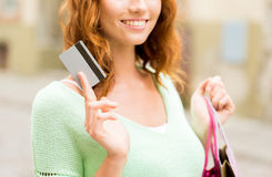 Close up of woman with credit card and bag. People, sale and consumerism concept - close up of happy woman with shopping bags and credit card on city street Royalty Free Stock Image