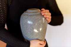 Close up of woman with cremation urn at funeral. Cremation, people and mourning concept - close up of woman with cinerary urn at funeral royalty free stock image