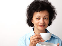 Close-up of a Woman with Cup. Close-up portrait of an elder smiling woman holding cup and saucer Royalty Free Stock Images