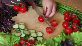 Close-up woman cuts cherry tomatoes on a wooden cutting board. Slow motion. Close-up woman cuts cherry tomatoes on a wooden cutting board, cucumbers, lettuce stock footage
