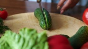 Close-up of a woman cuts in half with a knife fresh cucumber on a cutting Board. Close-up of a woman cuts in half with a knife fresh cucumber on a wooden stock video footage
