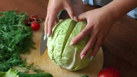 Close-up of a woman cuts a knife in half cabbage on a cutting board. Close-up of a woman cuts a knife in half cabbage on a wooden chopping board on a black stock video footage