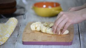 Close-up on woman cutting banana on cutting board. On a wooden table on a cutting board, a woman slicing a banana with knife. Slow motion stock footage