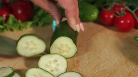 Close-up of a woman cutting a fresh cucumber on a wooden cutting Board. Close-up of cook cutting fresh cucumber on wooden chopping Board, slow motion. Cooking stock video