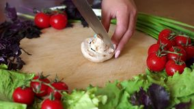 Close-up of a woman cutting mushrooms on a round wooden cutting board. Close-up of a woman cutting mushrooms on a round wooden cutting board, next to a lot of stock footage