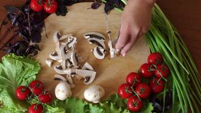 Close-up of a woman cutting mushrooms on a wooden chopping board. Top view. stock video footage
