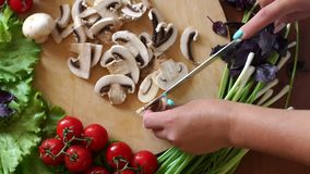 Close-up of a woman cutting mushrooms on a wooden chopping board. Top view. Close-up of women`s hands cut with a knife mushrooms on a wooden cutting board, on stock video