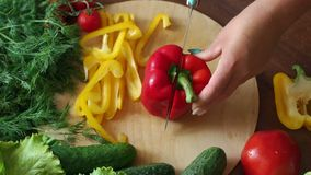 Close-up of a woman cutting ripe juicy red pepper on a wooden board. Close-up of a woman cutting ripe juicy red pepper on a wooden board, in the background are stock footage