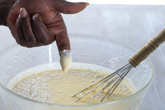 Close-up of woman dipping her finger in the baking Mixture Stock Photos