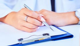 Close up of woman doctor taking notes. Photo with dept of field. Close up of woman doctor hand taking notes. Photo with dept of field stock photo