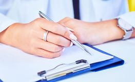 Close up of woman doctor taking notes. Photo with dept of field. Close up of woman doctor hand taking notes. Photo with dept of field royalty free stock photo