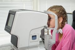 Close up of woman doctor working with the refractometer machine. A little girl having her eyes tested.  royalty free stock image