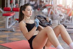 Close up of woman doing abs exercises with weight plate while sitting on sport mat on gym floor. Side view, sporty girl wears stock photo