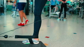Close-up - woman doing kick the feet with weighting. Woman doing kick her feet with weighting. Two feet on the mat. Girl doing exercise on the buttocks. The stock video