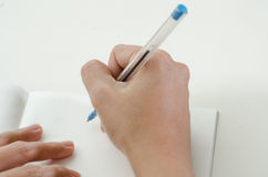 Close-up of a woman drawing into her diary. By ballpoint pen Royalty Free Stock Image