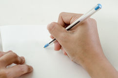 Close-up of a woman drawing into her diary. By ballpoint pen Royalty Free Stock Images