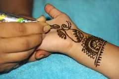 Close-up of woman drawing mehendi or tattoo on little girl`s palm. Pune stock images